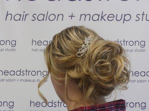 Blonde up-do with a decorative hair piece to secure the veil