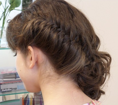 Brunette with a side style up-do and a braid at Headstrong Salon
